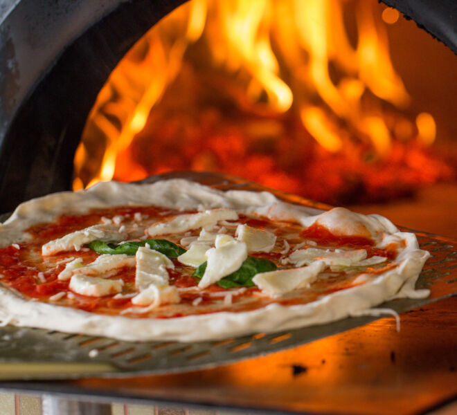 italian pizza getting in a wood burning pizza oven.
