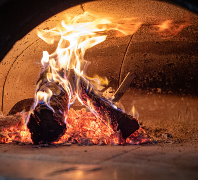 Flames, logs, ashes, embers inside wood burning pizza oven